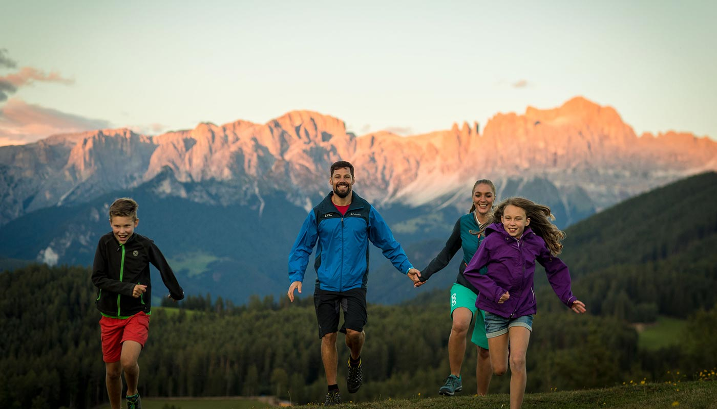 A family on a hike through the Dolomites' meadows