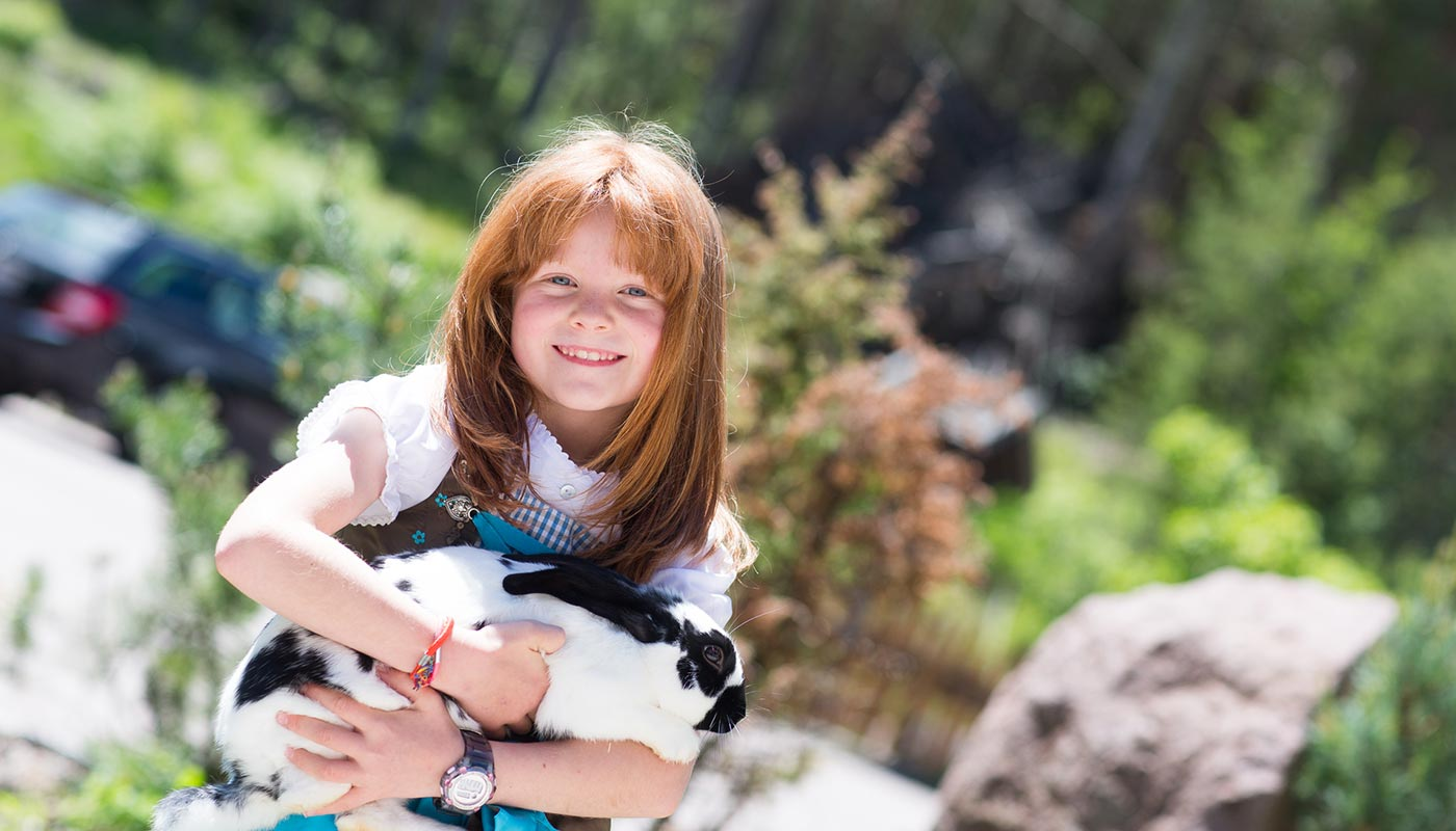 A little girl is holding a rabbit in her arms at Hotel Wieslhof