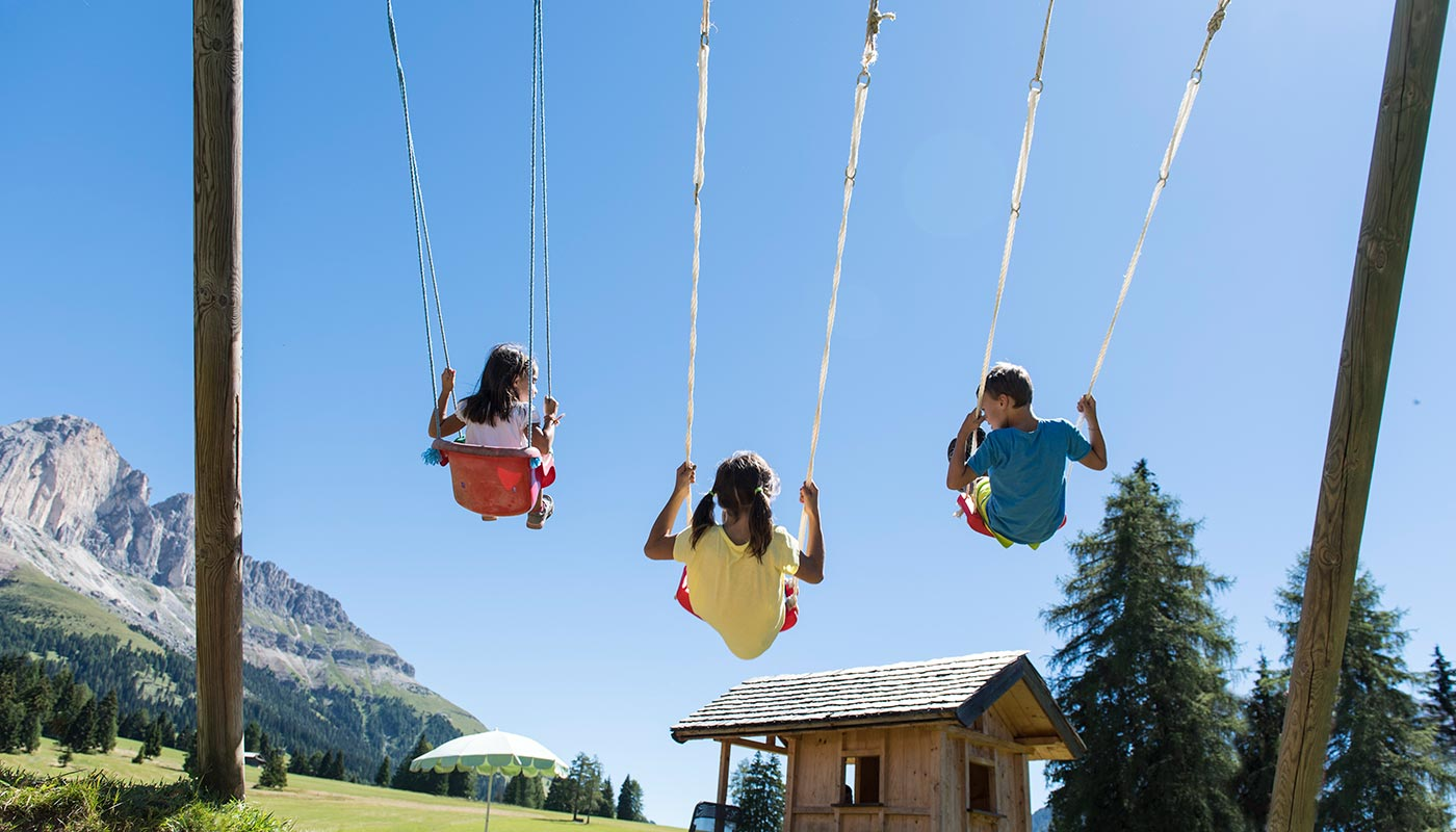 Three children are on the swing during their family holiday