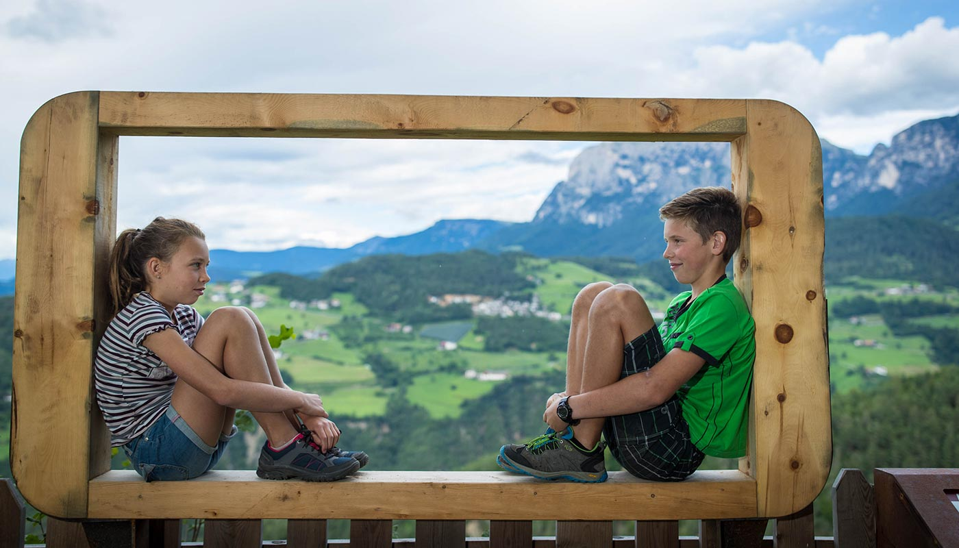Two children sit on a fence and in the background Val d'Ega