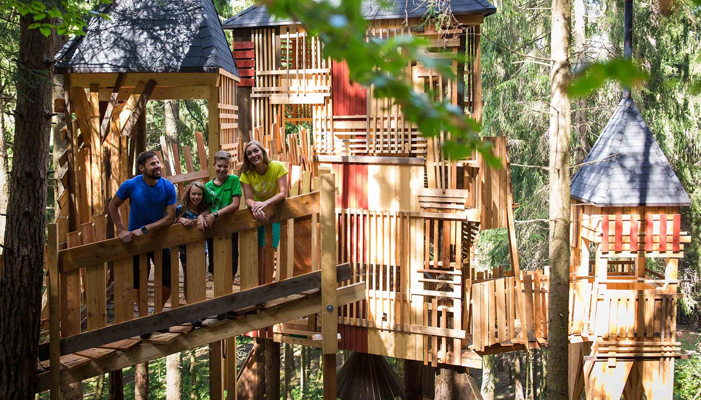 A familys has fun in one of the playgrounds around the Dolomites Family Hotel