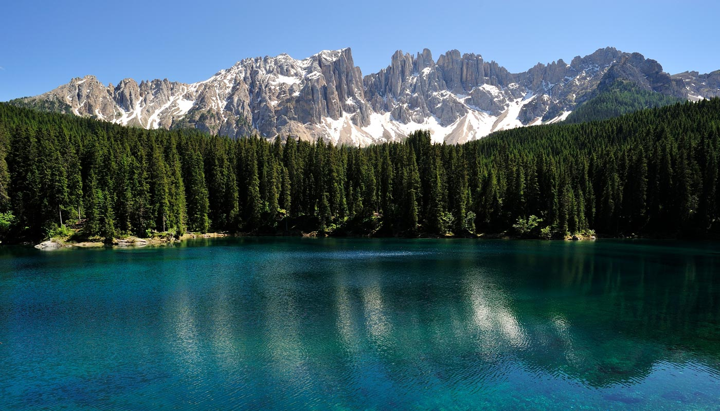 View of Lake Carezza and in the background the snowy Dolomites