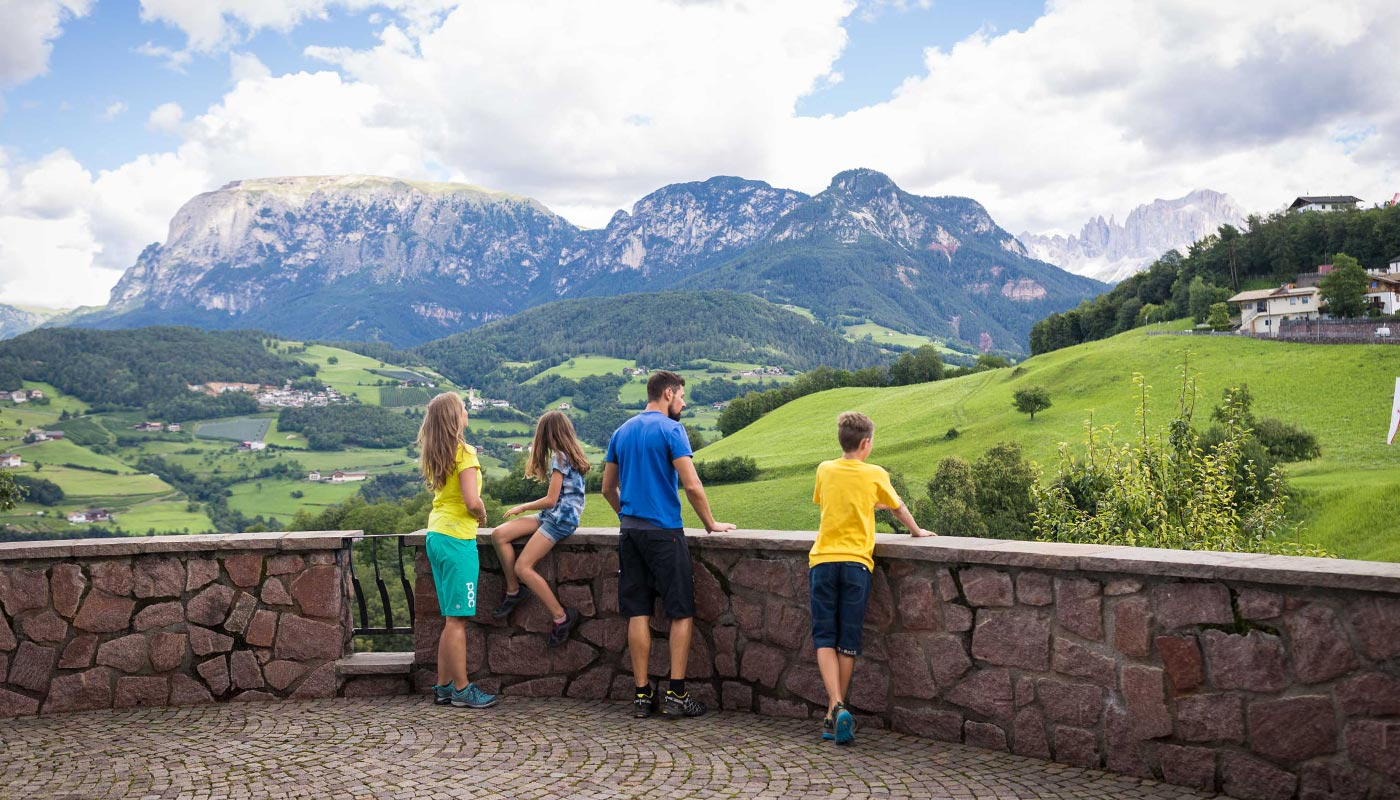 A family enjoys the view of Val d'Ega in South Tyrol