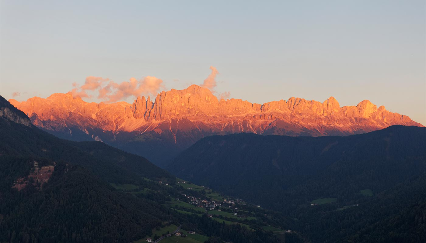 View of the Val d'Ega and in the background the Dolomites illuminated by the light of sunset